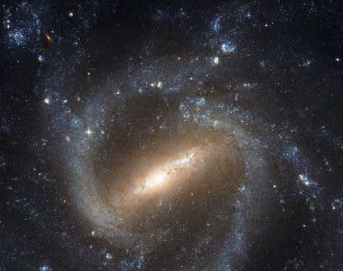 Image of a Barred-Spiral Galaxy. Just below center is the elongated central bar tilted about 45-degrees from the bottom of the frame. At each end of the bar begin the spiral arms, twisting clockwise around the central bar and encircling the whole galaxy.