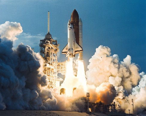 Photograph of the Space Shuttle Discovery at liftoff.