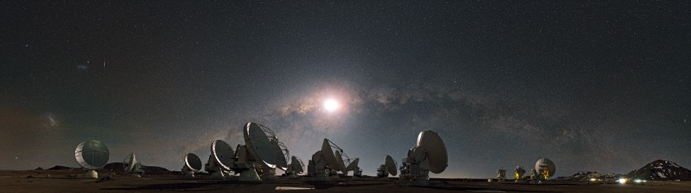 Photograph of the Atacama Large Millimeter Array in Chile, taken at night. Many of the telescopes are seen pointing in various directions, with the Moon and Milky Way prominent in the background sky.