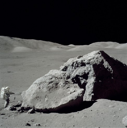 Scientist on the Moon. Photograph of geologist Harrison Schmitt collecting samples near a large boulder on the Lunar surface. Schmitt is at lower left, dwarfed by the massive boulder.