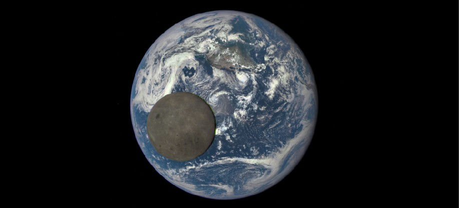 Image of the Moon Crossing the Face of the Earth. The dark disk of the Moon lies in front of the bright, cloud covered Earth illustrating the difference in relative brightness between the two bodies.