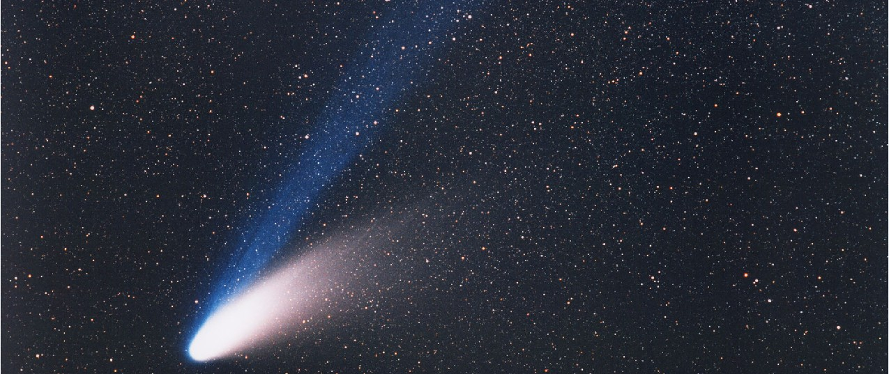 Comet Hale-Bopp. In this photograph the bright nucleus is seen at lower left, with the white dust tail curving away toward center-right. The blue ion tail moves away from the nucleus straight toward the top-center of the image.