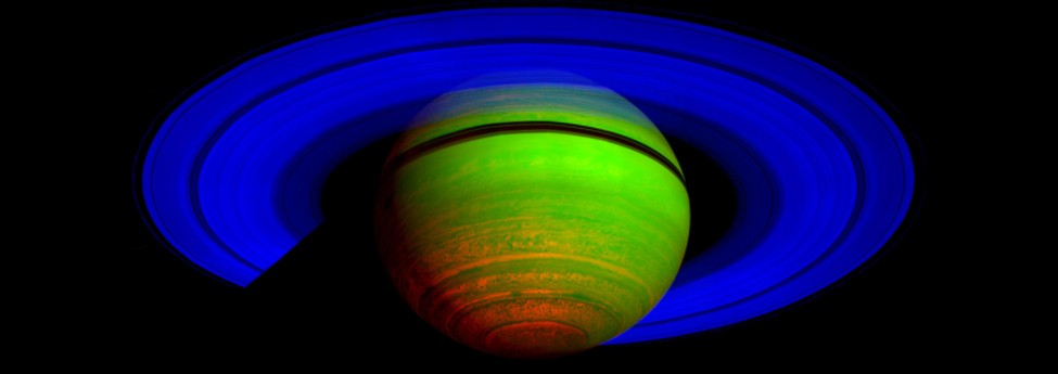 An image of Saturn seen in infrared. The rings are shown in blue, and the planet sphere is mostly green with some red at the bottom and a black ring around the upper top of the sphere.