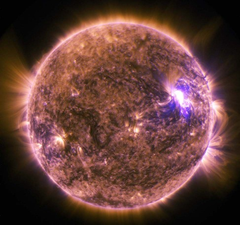 An image of a solar flare, a bright region to the right of the sun.