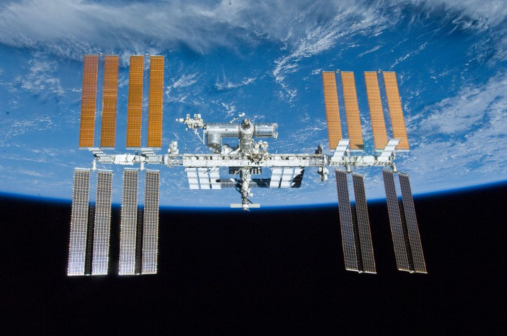 An image of the International Space Station floating in front of a portion of the globe of Earth.