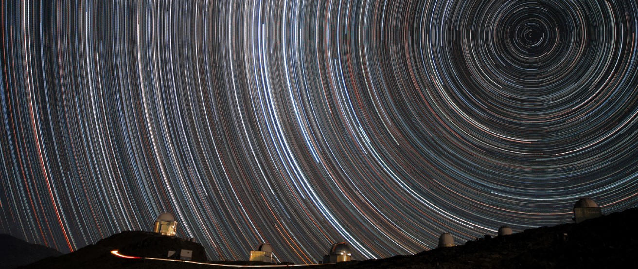 Time exposure photograph of the night sky, showing stars as semi-circular streaks of light, rather than points, due to the rotation of the Earth.