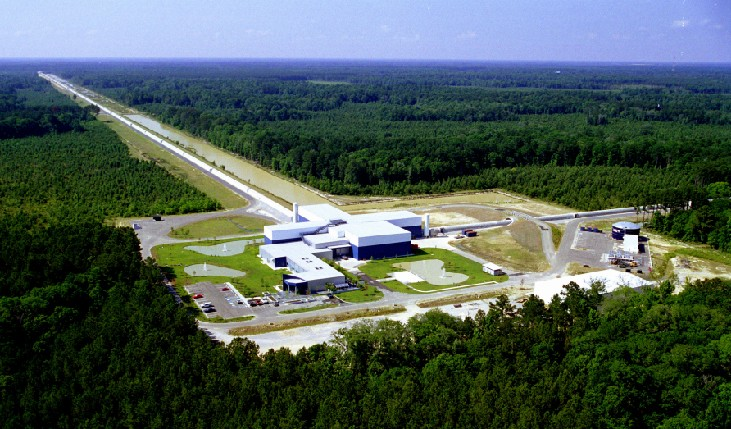 Aerial Photograph of the LIGO Facility. The main building is shown at center, with one of the 4-km long tubes extending toward the horizon at upper left. A portion of the other tube is seen at right.