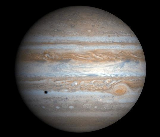 Photograph of Jupiter. Taken from the Cassini spacecraft, the alternating light and dark cloud bands are visible over the entire planet. The Great Red Spot is at lower right. Also seen is the shadow of the moon Europa at lower left.