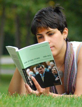 A young woman reading a textbook.