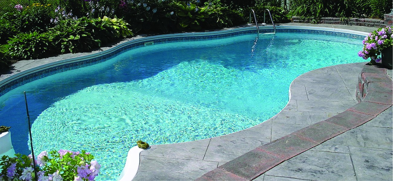 This figure shows a swimming pool that is full of water and surrounded by a concrete patio.