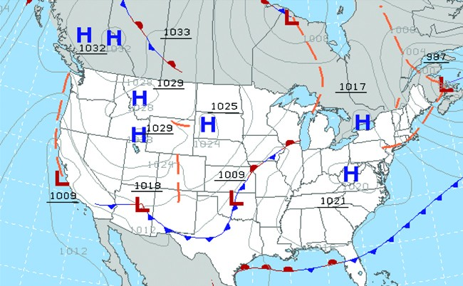 A weather map of the United States is shown which points out areas of high and low pressure with the letters H in blue and L in red. Curved lines in grey, orange, blue, and red are shown. The orange lines are segmented. The red and blue lines have small red or blue semi-circles and triangles attached along their lengths. In dashed white lines, latitude and longitude are indicated. Underlined three and four digit numbers also appear across the map.