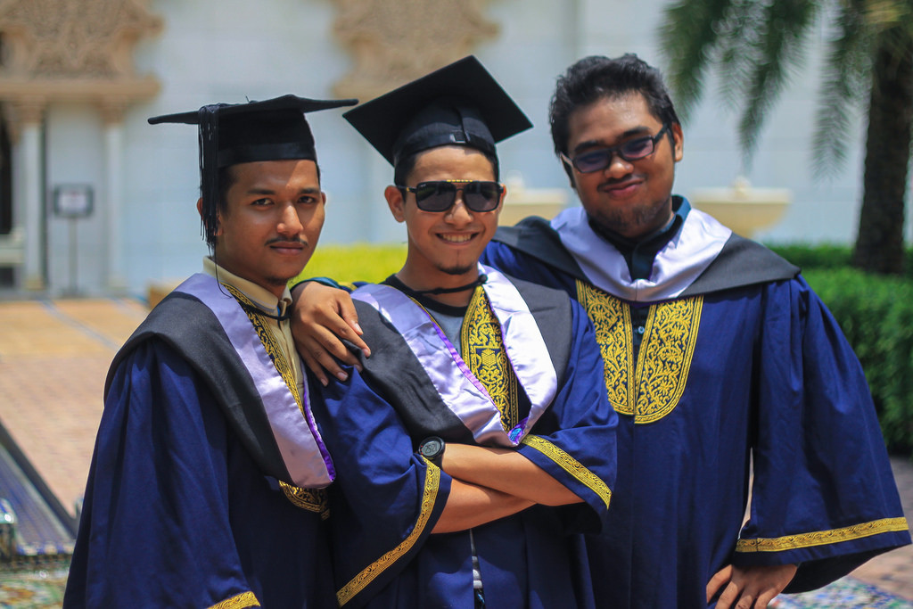 Photo of three young men with their arms around one another, smiling, in graduation caps and gowns.