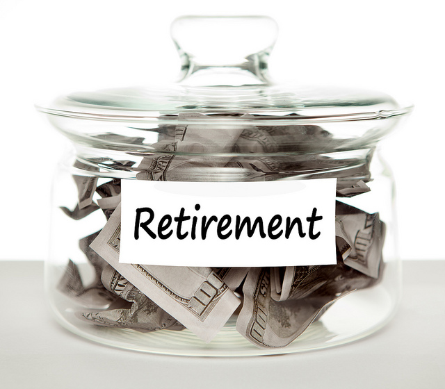 "Glass jar labeled ""Retirement."" Inside are crumpled $100 bills"