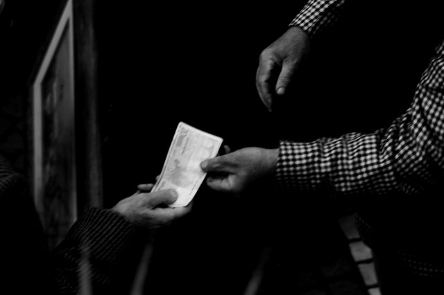 Black and white aerial shot of hands exchanging money