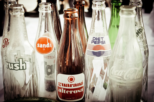 collection of empty glass soda bottles