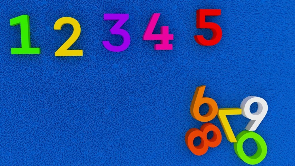 Blue background with magnetic numbers attached to it. 1-5 are arranged sequentially at the top, while remaining digits are clustered at the bottom right