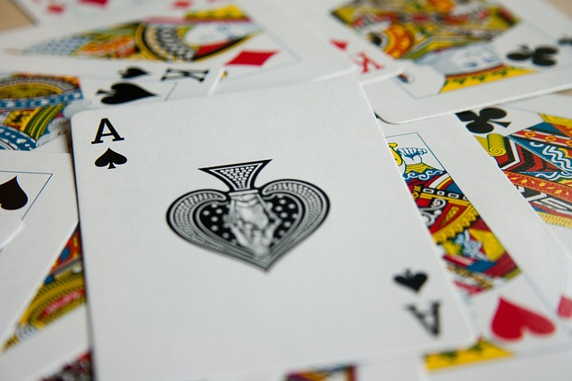 scattered playing cards on a table. The Ace of Spades is on top.