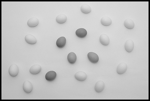 Black and white photo of eggs on a table. They range in hue from white to dark grey