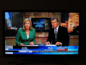 Image of a male and female newscaster delivering the news from a TV set.