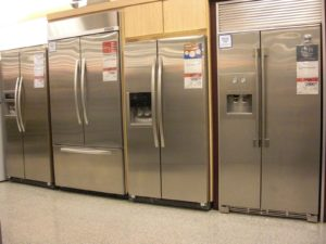 Four new refrigerators with price tags in a store