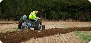 Fazendeiro que lavra um jardim usando um trator.