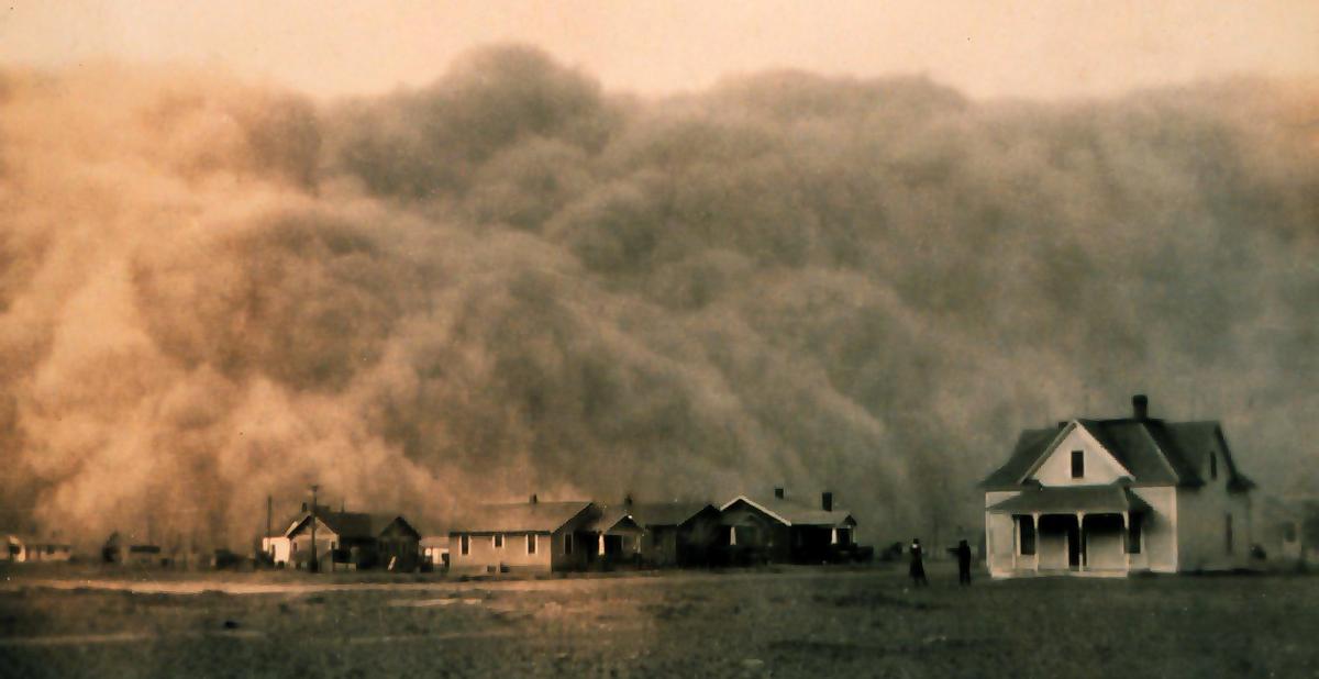 Tempestade de poeira se aproximando de Stratford, Texas. Bacia de poeira que examina em Texas. As nuvens de poeira são três a quatro vezes a altura das casas da fazenda na foto.