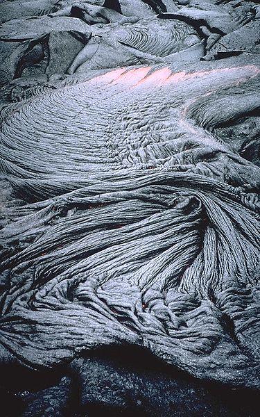 Ideia próxima da textura ropy que forma na superfície de um fluxo do pahoehoe no vulcão de Kilauea, `i de Hawai.