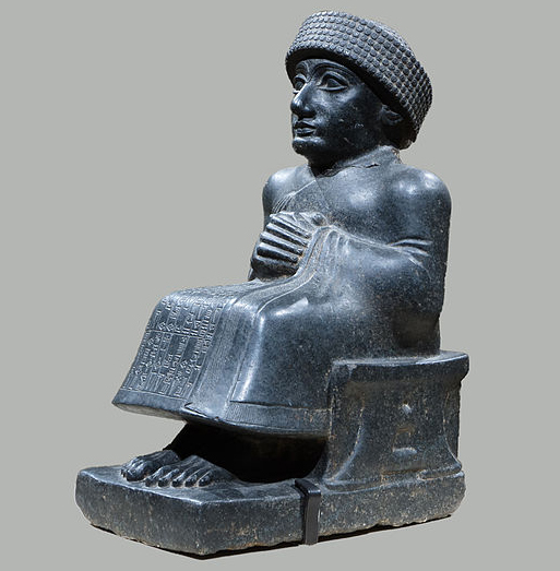 A stylized statue made of black stone.