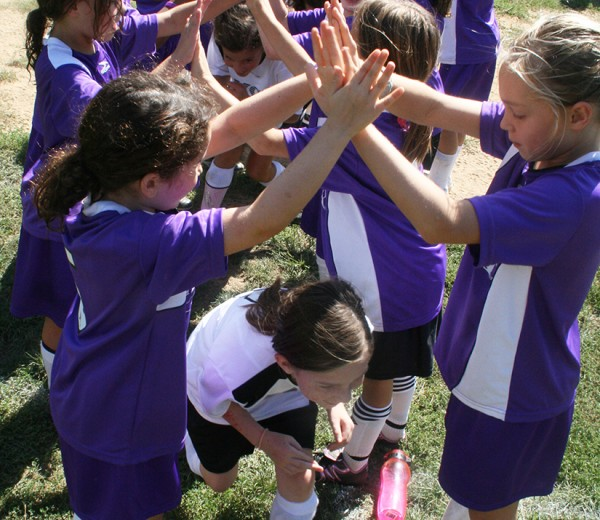 A photo young girls dressed in soccer uniforms forming a tunnel with their hands for which other girls run through as a post-game ritual.