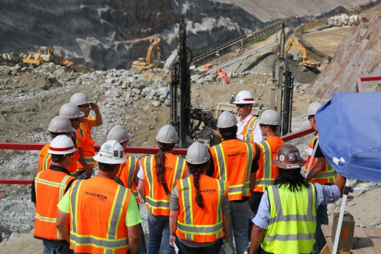 Students wearing bright orange and yellow construction vests are shown standing around an outdoor job site.