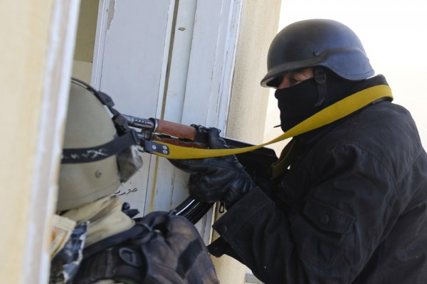 An armored police officer is shown in a doorway holding and pointing his gun.