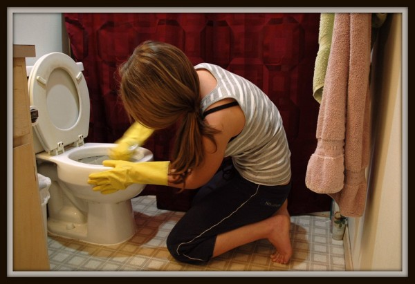 A woman is shown kneeling on a bathroom floor scrubbing a toilet.