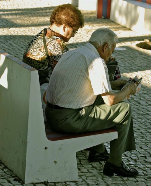 An elderly man and woman are shown sitting on a bench.