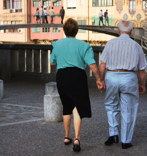 In figure (a), an older man and woman, wearing casual dress, are shown from behind walking in a public plaza setting.