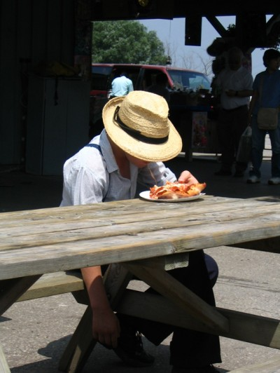 A young Mennonite boy in a straw hat is shown eating a piece of pizza.