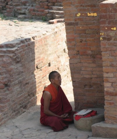 A man dressed in an orange robe is shown with his legs crosses, sitting within outdoor brick walls.