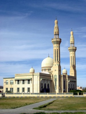 A mosque is shown, a large building with one large dome and two smaller domes and two towers, called minarets.