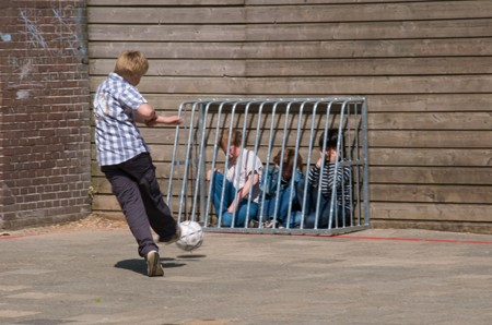 Boy kicking a soccer ball on a playground toward three other boys who are caged against a wall by a small metal goal post. The boys are crying or holding their ears.