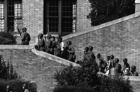 Armed National Guardsmen escorting black students up the outside stairs of a brick high school building.
