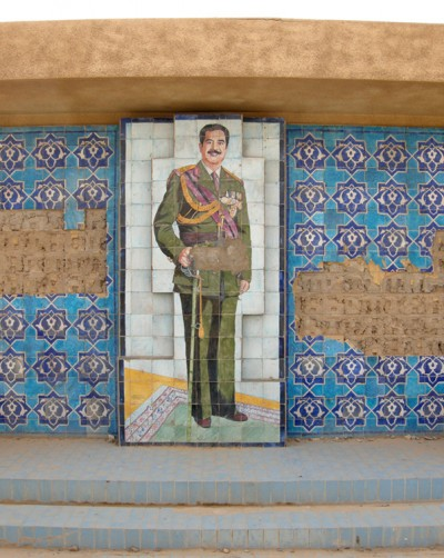 A mosaic of Saddam Hussein and other tile decorations are shown on a wall.