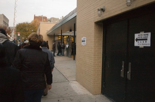 "People are shown standing outside a building in line. Signs on the building read ""vote here"" in various languages."