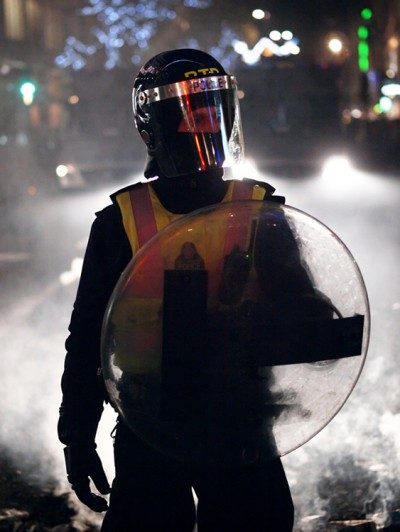 A masked officer with a shield is shown here.