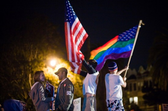 Figure (c) shows people waving a U.S. flag and a rainbow flag.