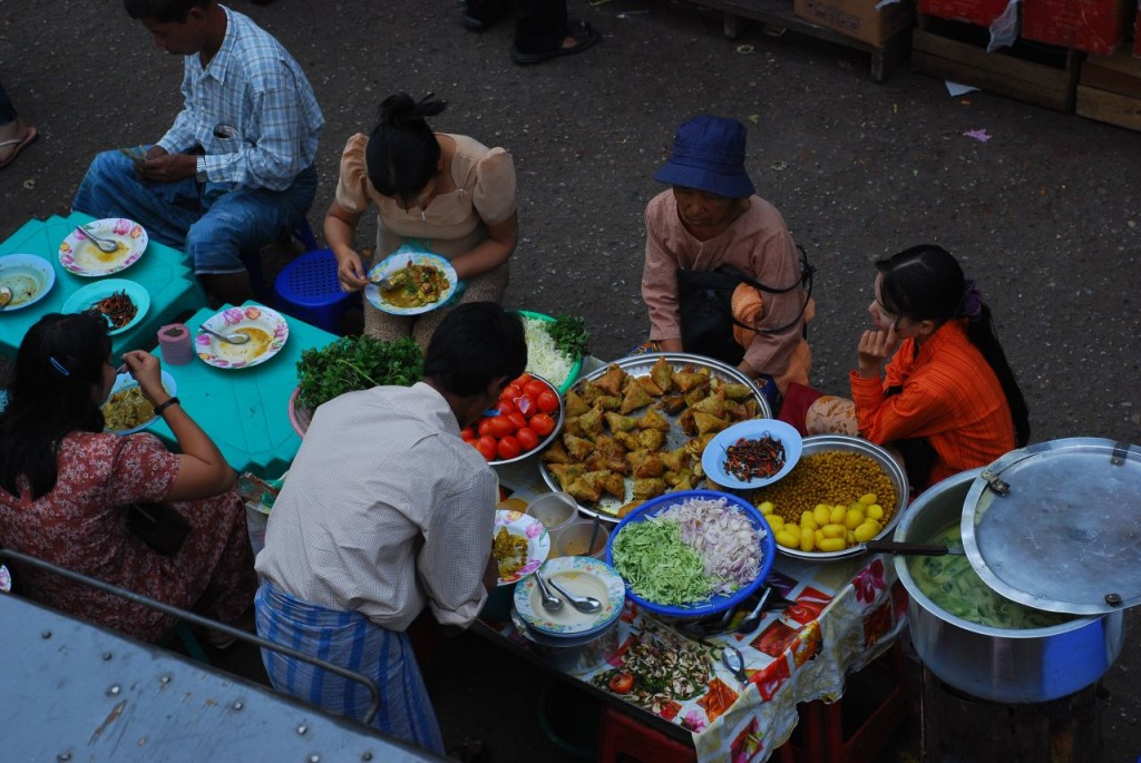 People eating outside on small benches at a table filled with large platters of colorful food.