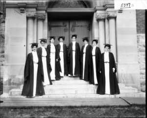 Eight women in dresses, caps, and gowns, standing on the steps of a college in a black in white photograph.