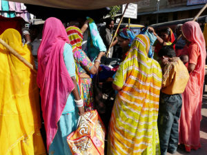 Photo showing the backs of women wearing saris while shopping in India.