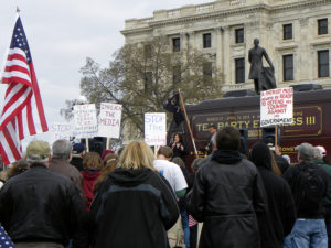 Tea Party protestors carrying pickets and an American flag.
