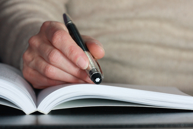 Photo of a hand holding a pen over an open book