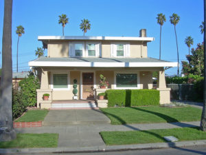 Stucco two story house with palm trees around it