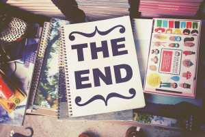 """Photo looking down on a pile of books, with a notebook labeled """"The End"""" on top"""